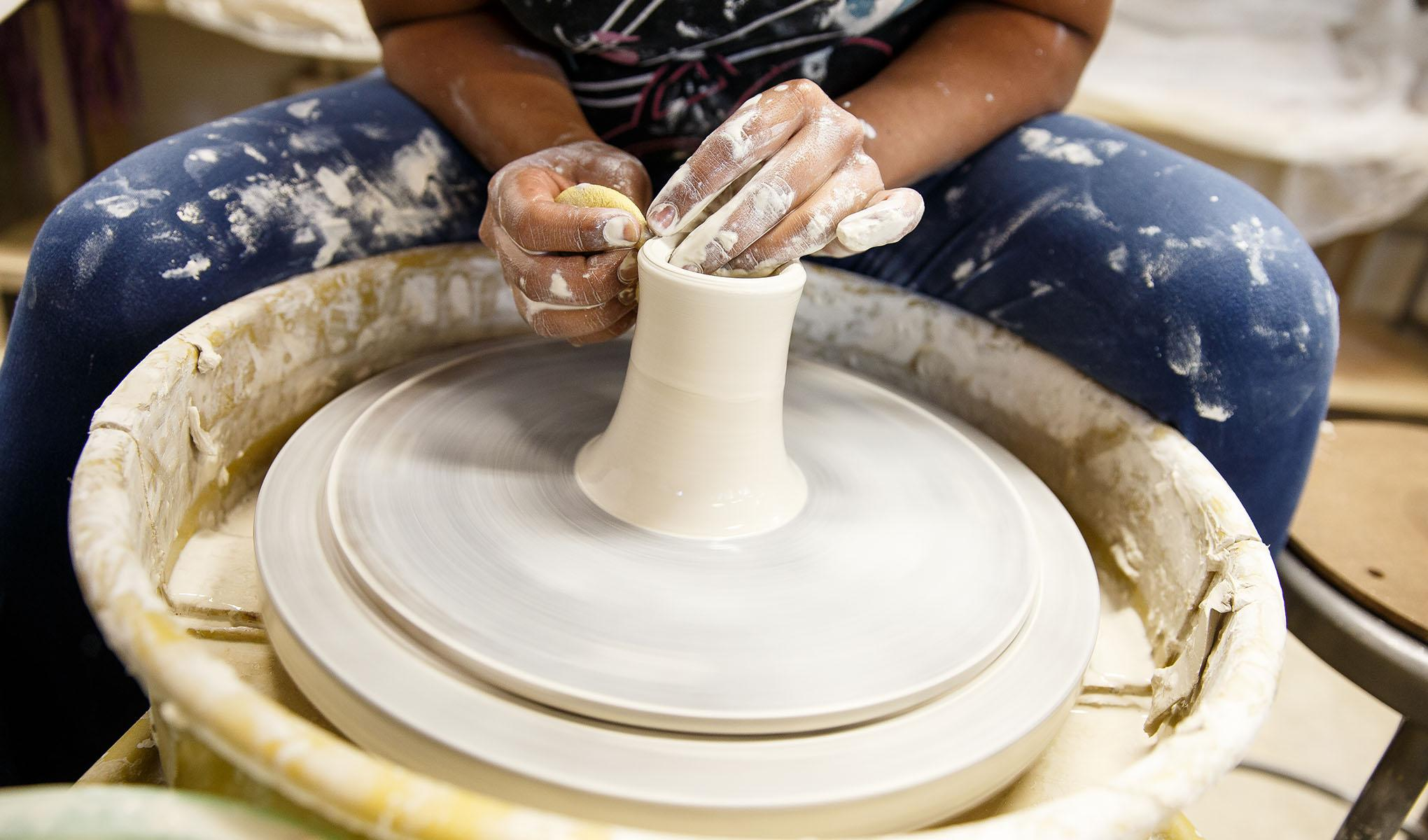 An SF State student uses a pottery wheel.