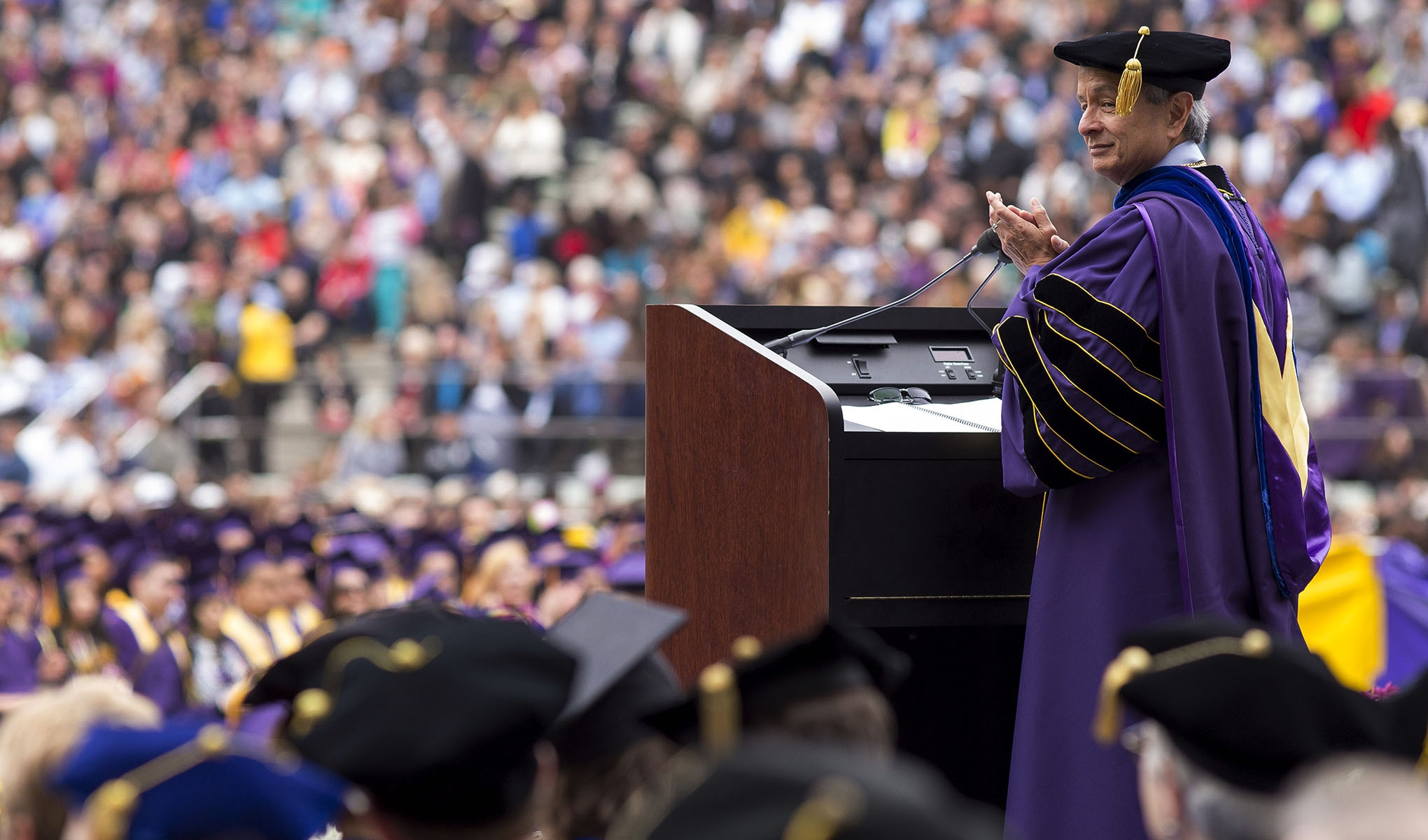 Leslie E. Wong stands at a podium in academic regalia with a crowd in the background
