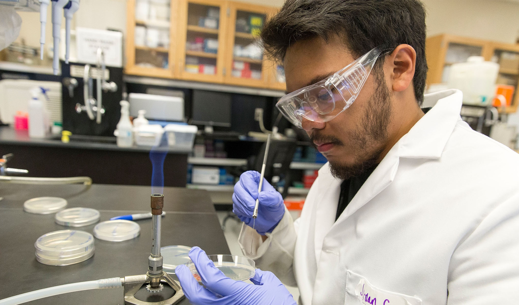 A man in a white lab coat and goggles prods a petri dish next to a small flame in a research laboratory.